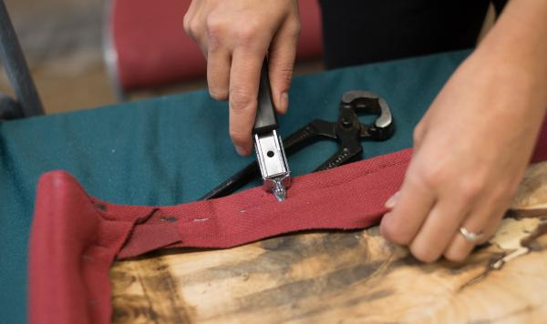 A repair specialist unpicks stitching at a Repair Cafe.